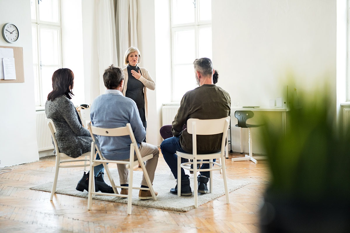 A senior woman standing and talking to other people during group therapy.